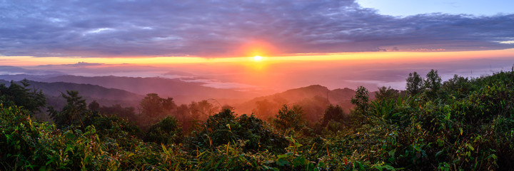 Panoramic view of sunrise with mist and mountain at Doi Pha Hom Pok  in Chiang Mai, Thailand.