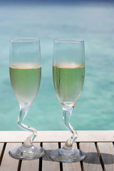 Two champagne glasses by the ocean