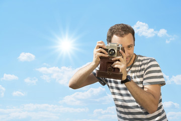 Young hipster man photographing with vintage camera.