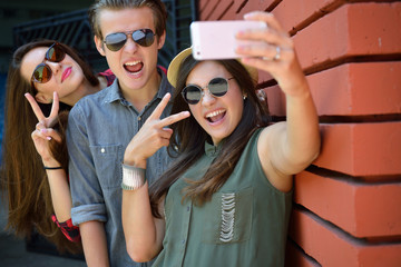 Young girls and boy having fun outdoor and making selfie with sm