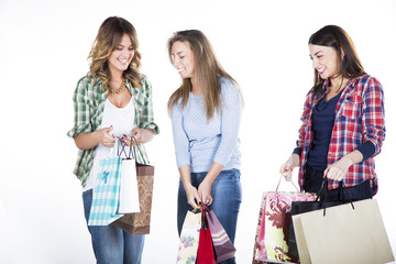 Group of three happy young adult women out of shopping with colorful bags