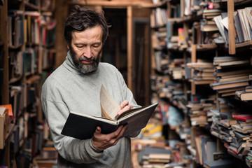 Portrait of authentic senior man on book market