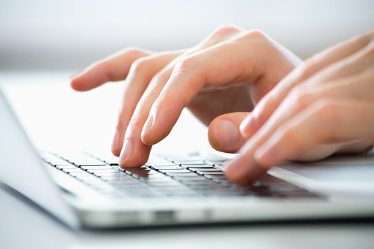 Close-up of hands of business man typing on a laptop.