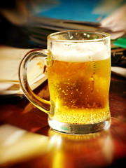 Lunch break-time.Beer glass on table with notebooks.Soft bokeh.
