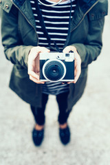 Young handsome woman holding a vintage camera