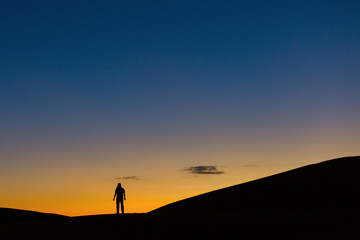 Sillhouette of man in desert at sunset