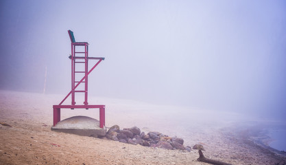 Empty beach lifeguard chair - lonely lifeguard seat stands empty on fog shrouded November beach in Ontario Canada.