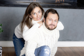 Portrait of husband and wife in white sweaters.