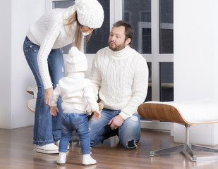 Family dressed in a white sweaters near the window.