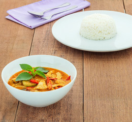 Red pork curry (Panang) with rice in white plate on wooden backg