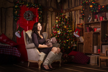 Woman sitting  with teddy bear  in christmas decorations