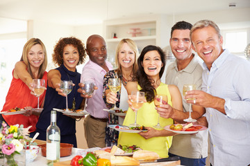Portrait Of Mature Friends Enjoying Dinner Party At Home
