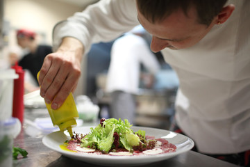 Chef garnishing salads in the kitchen garnishing their salads