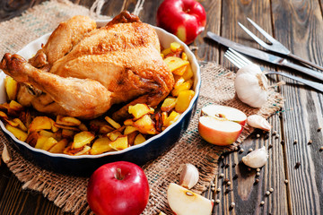 Baked chicken with baked potatoes , apples , garlic and spices on a wooden background