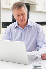 Concerned Senior Man Looking At Finances On Laptop