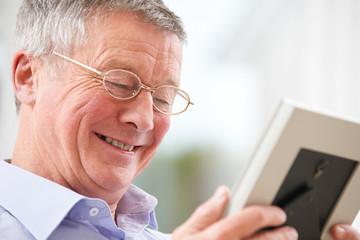 Smiling Senior Man Looking At Photograph In Frame