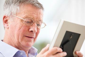 Unhappy Senior Man Looking At Photo In Frame