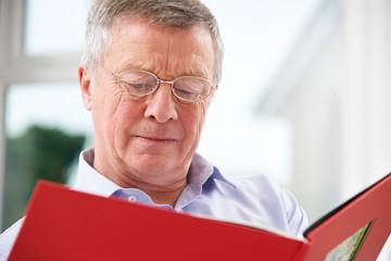 Sad Senior Man Looking At Photo Album