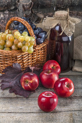 Black and white grapes with red apples and fresh juice on rustic table and in front of the wood
