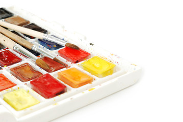 Bright used watercolor paints in box and  brushes isolated on a white background. Macro shot