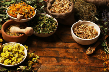 Assortment of dry medicinal herbs in bowls on wooden background top view