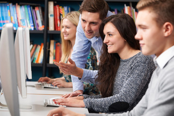 Tutor Helping Teenage Students Working At Computers