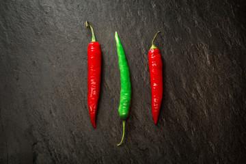 Drei rote und grüne Peperoni auf Platte aus Naturschiefer
