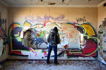 Un homme de dos au dans un bâtiment rempli de graffitis