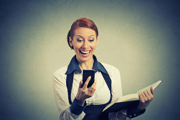 happy young woman holding book looking at phone seeing good news
