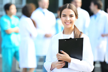Beautiful young woman doctor with clipboard in hands against group of medics