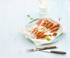 Roasted young carrots with cream and seeds in ceramic plate over blue wooden background
