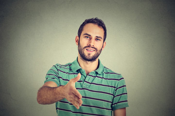 Casual man offering handshake isolated on gray wall background
