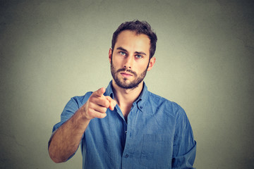 Portrait of a angry young man pointing finger at you camera gesture