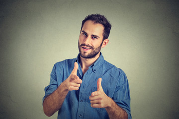 handsome young man giving thumbs up pointing fingers at camera, picking you