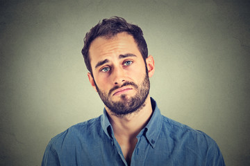 Portrait of a sad young man isolated on gray wall background