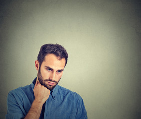 Sad depressed young man holding head with hand looking down