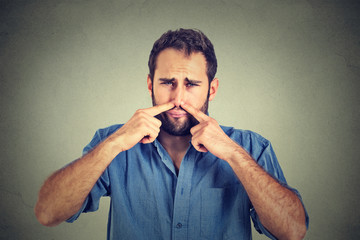 disgusted man pinches nose with fingers hands looks with disgust something stinks