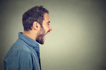 Side profile portrait of young angry man screaming