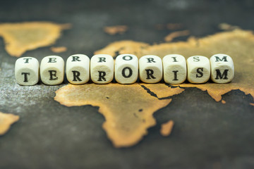 Wooden blocks with the text, TERRORISM, on the background of world map