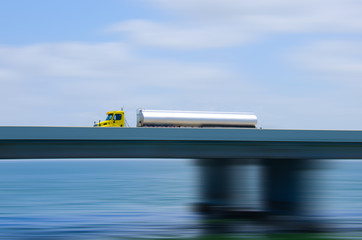 Eighteen wheeler semi tractor truck tanker pulling a petroleum fuel tank over a bridge with a motion blur background showing extreme speed. Very colorful green and blue water and sky in the background