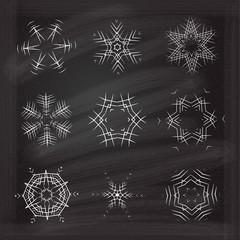 Ornamental snowflakes set on chalkboard background.