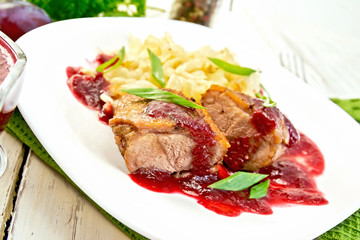 Duck breast with plum sauce and cabbage in plate on green napkin