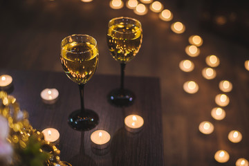 two vine glasses with many candles
