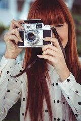 Attractive hipster woman using old fashioned camera