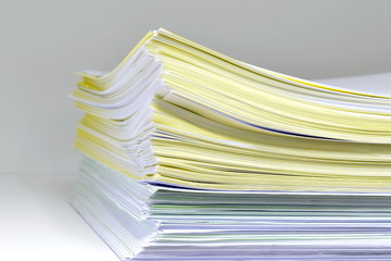 Documents on bookshelf/Documents on white wooden bookshelf.