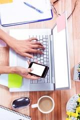 Overhead of feminine hands using laptop and smartphone