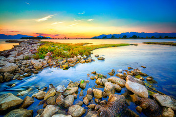 Beautiful summer sunset over the rocky shore by sea. HDR image