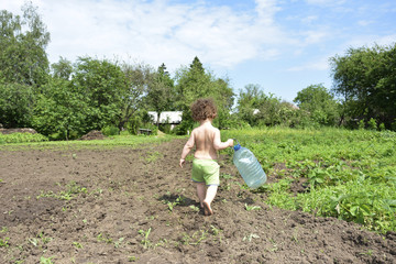 In summer, a small rural curly girl holding a large plastic bott