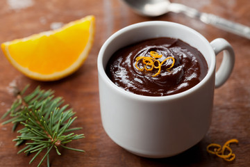 Delicious dessert from dark chocolate mousse with orange slice decorated citrus peel on rustic table