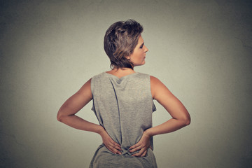 young woman standing with backache back pain